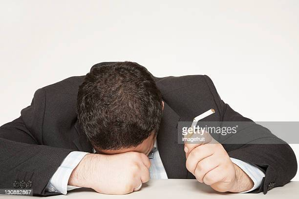 quitting is hard: frustrated man holding broken cigarette - smoking crack stock photos and pictures