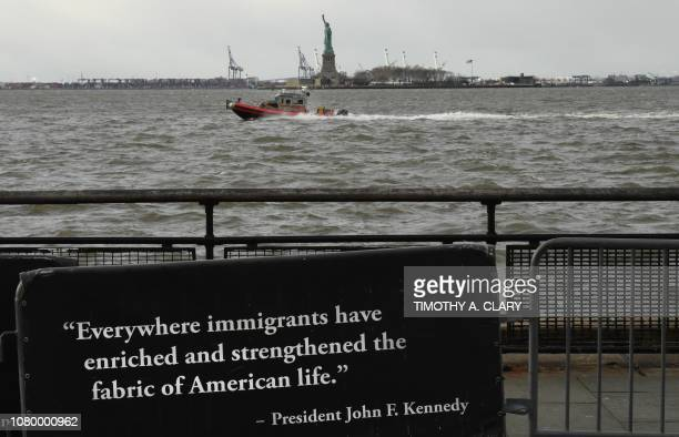 A quote on a banner in Battery Park from former US President John F Kennedy as boat passes by the Statue of Liberty on January 10 2019 New York...
