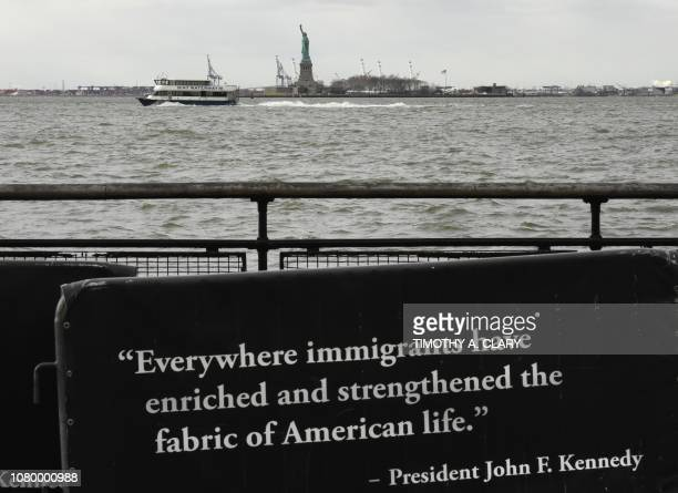 A quote on a banner in Battery Park from former US President John F Kennedy as ferry passes by the Statue of Liberty on January 10 2019 New York...