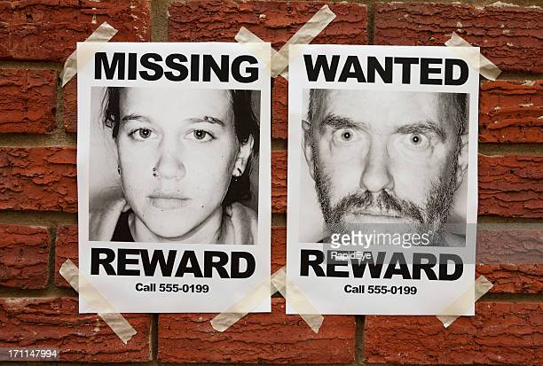 """Missing"" and ""Wanted"" posters taped to brick wall"
