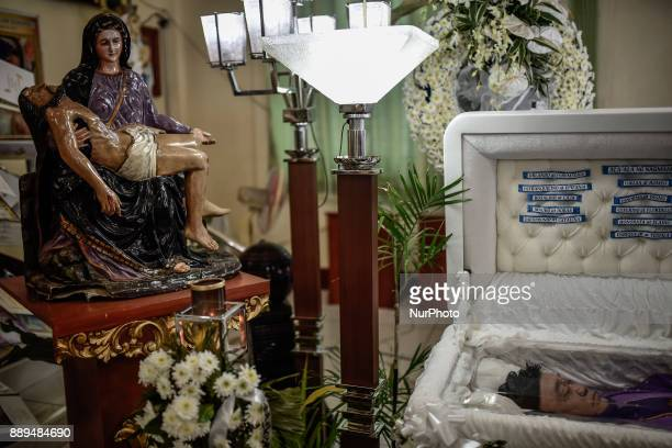 A quotpietaquot statue is seen next to the coffin of activist priest Marcelito quotTitoquot Paez who was killed by unidentified assailants during his...