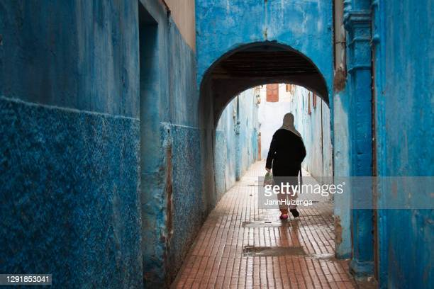 rabat, morocco: woman in blue alleyway in medina - rabat morocco stock pictures, royalty-free photos & images