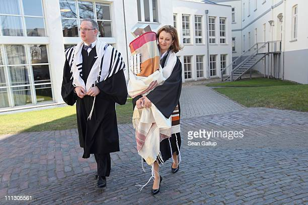 Rabbi Alina Treiger , accompanied by Lower Saxony state Rabbi Jonah Sievers, carries a torah scroll back to the small synagogue in Oldenburg...