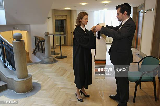 Rabbi Alina Treiger gets a little help from her husband Jona Simon who is also studying to become a rabbi with a tallit prayer shawl moments before...