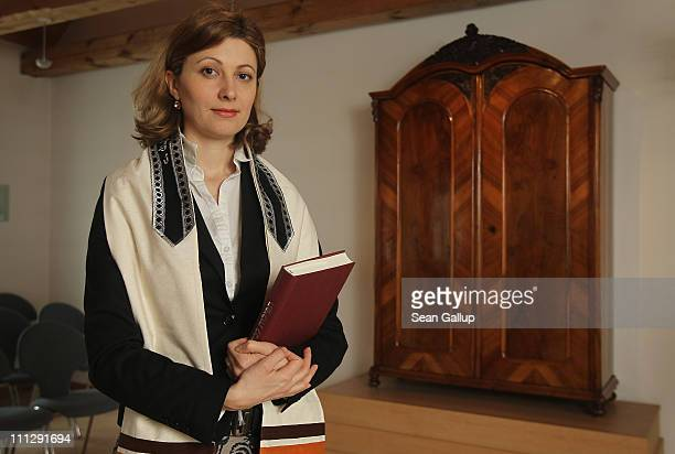 Rabbi Alina Treiger poses with a Jewish prayer book and wearing a tallit prayer shawl next to the cabinet that contains torah scrolls in the small...