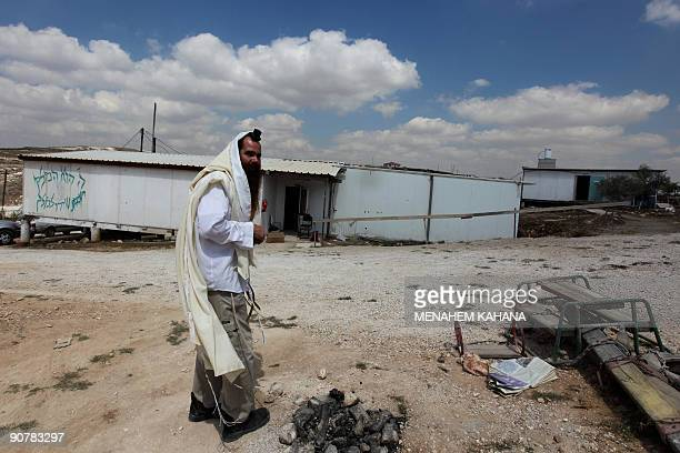 MOSER Rabbi Arie Lipo wears a prayer shawl as he walks into the Yeshiva in the illegal Jewish outpost of Havat Gilad near the West Bank city of...