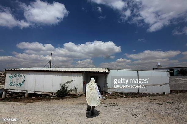 MOSER Rabbi Arie Lipo wears a prayer shawl as he walks into the Yeshiva of the illegal Jewish outpost of Havat Gilad near the West Bank city of...