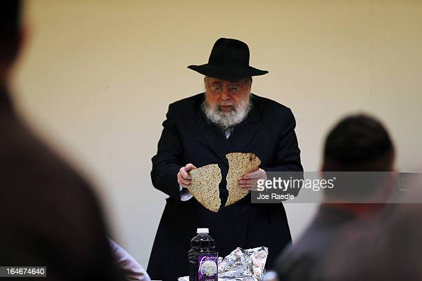 Rabbi Efraim Katz breaks a piece of matzo as he leads a community Passover Seder at Beth Israel synagogue on March 25 2013 in Miami Beach Florida The...