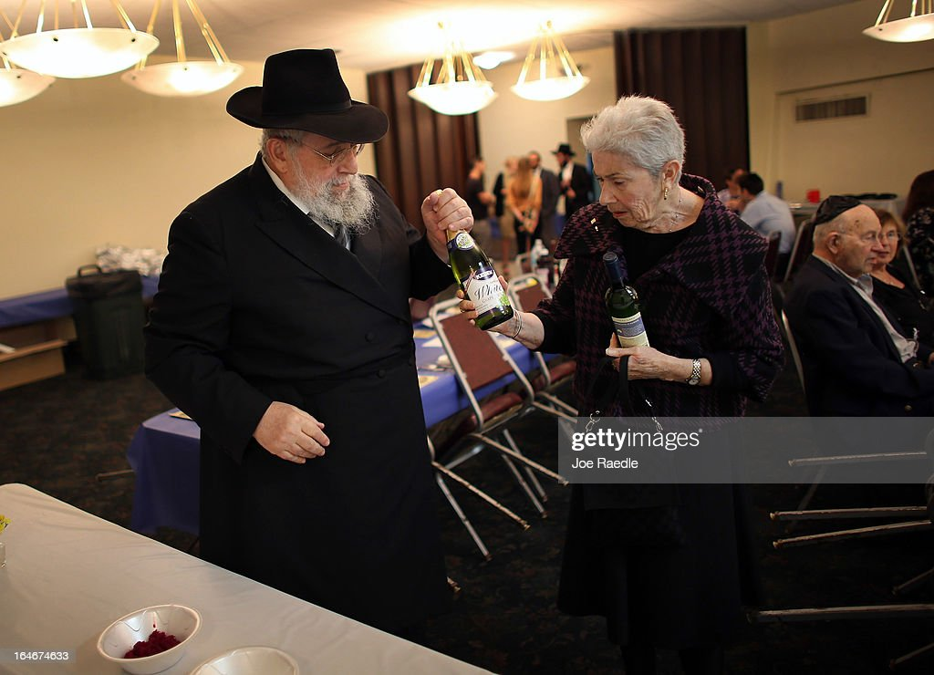 Rabbi Efraim Katz gives wine to Pauline Kopelman to be placed on a table as he leads a community Passover Seder at Beth Israel synagogue on March 25, 2013 in Miami Beach, Florida. The community Passover Seder that served around 150 people has been held for the past 30 years and is welcome to anyone in the community that wants to commemorate the emancipation of the Israelites from slavery in ancient Egypt.