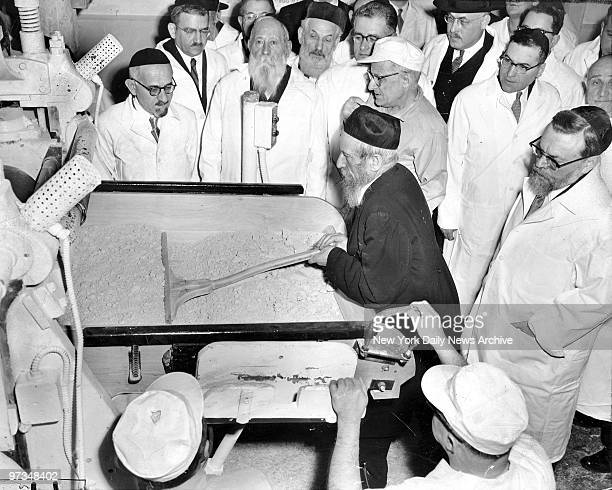Rabbi Eliezer Silver inaugurates prePassover season by pushing batch of dough through oven to bake matzo at B Manischewitz factory in Jersey City NJ...
