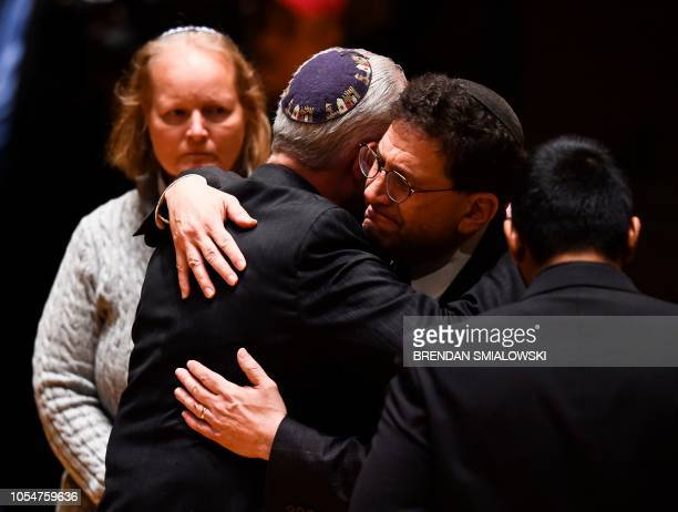 Rabbi Hazzan Jeffrey Myers from the Tree of Life synagogue hugs other religious leaders during a vigil to remember the victims of the shooting at his...