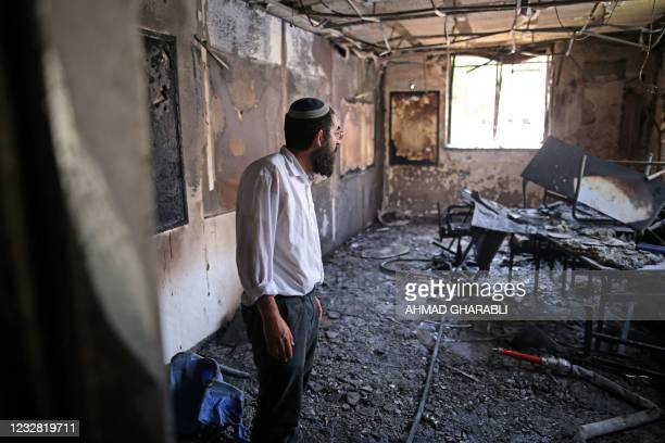 Rabbi inspects the damage inside a torched religious school in the central Israeli city of Lod, near Tel Aviv, on May 11 following night clashes...