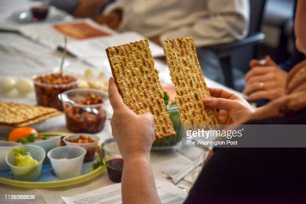 Rabbi Janet Ozur Bass breaks a piece of unleavened bread at an Interfaith Passover seder hosted by Montgomery County council member Sidney Katz at...