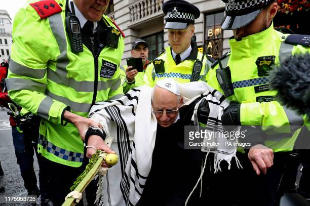 Rabbi Jeffrey Newman is arrested as protesters continue to block the road outside Mansion House in the City of London, during an XR climate change...