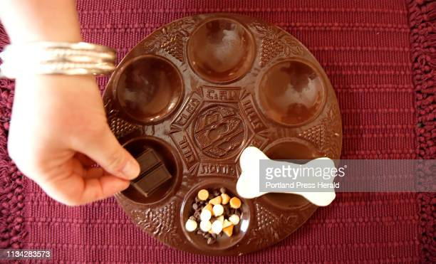 Rabbi Laura Boenisch of Bnai Portland demonstrates adds baker's chocolate to a milk chocolate Seder plate at her Falmouth home The unsweetened...