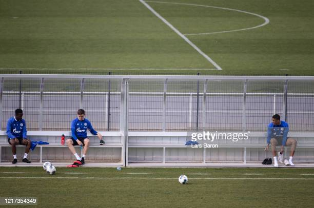Rabbi Matondo and Bastian Oczipka hold distance while changing their shoes during a training session at FC Schalke 04 training ground on April 07,...