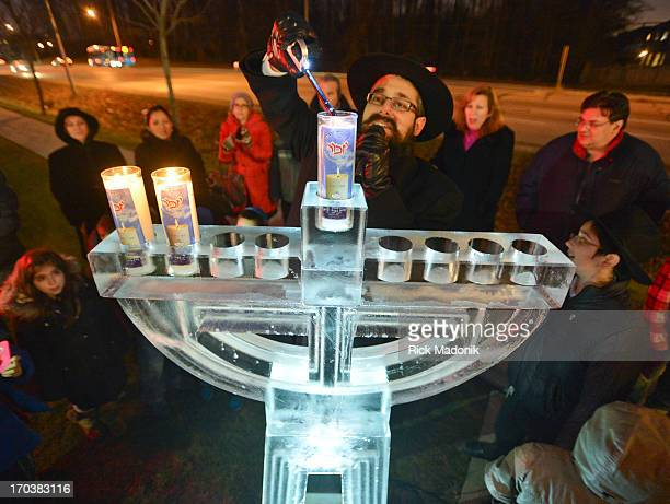 121209 THORNHILL ONTARIO Rabbi Mendel Kaplan lights the ice mennorah in front of members of his congregation of Chabad on Flamingo in Thornhill...