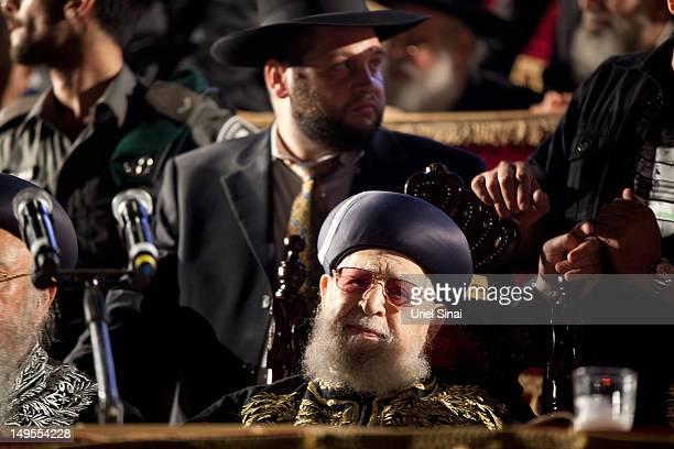 Rabbi Ovadia Yosef spiritual leader of the Israeli ultraOrthodox Shas party is surrounded by other rabbis on a stage as tens of thousands of Ultra...