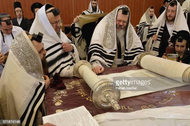 rabbi reading torah before hasidic congregation - rabbi stock pictures, royalty-free photos & images