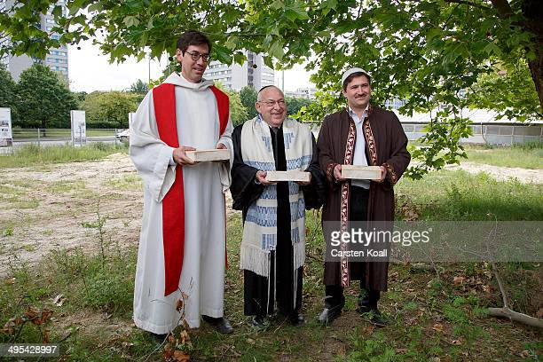 Rabbi Tovia BenChorin Father Gregor Hohberg and Imam Kadir Sanci hold symbolic bricks in their hands while standing at the construction site of the...