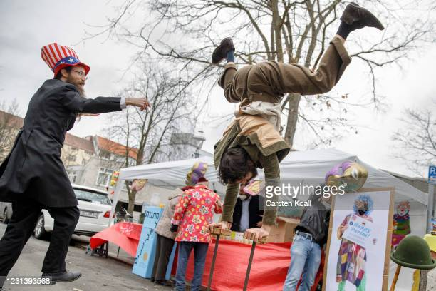 Rabbi Yehuda Teichtal dances beside an acrobat as members of the Chabad Berlin Jewish community pick up a package of gifts and goodies to celebrate...