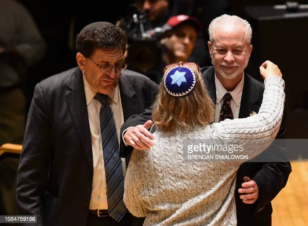 Rabbis hug during a vigil to remember the victims of the shooting at the Tree of Life synagogue the day before at the Allegheny County Soldiers...