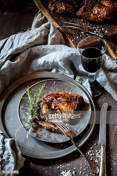 Rabbit legs on plate, thyme, rosemary and sea salt, red wine glass