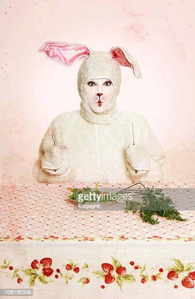 rabbit woman eating carrots at table - dirty easter stock pictures, royalty-free photos & images