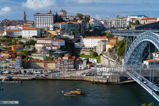 Rabelo port wine barge and The Ponte de Dom Luis I - metal arch bridge over River Douro connecting Porto to V|la Nova de Gaia, Portugal.