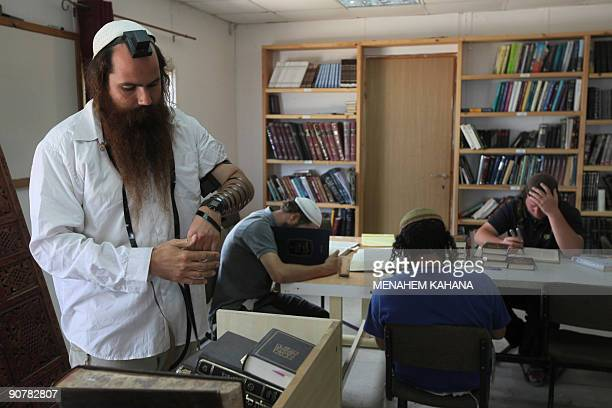 MOSER Rabi Arie Lipo wears Phylacteries in the Yeshiva of the illegal Jewish outpost of Havat Gilad near the West Bank city of Nablus on September 14...
