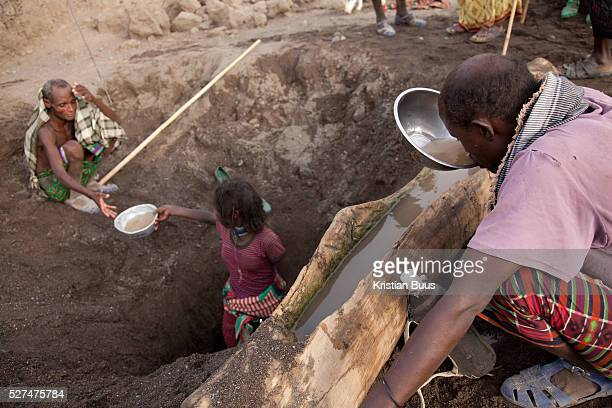Rabia is handing up a bowl of muddy water from below the river bed It's dry season in Afar and water is hard to come by Here a hole has been dug into...