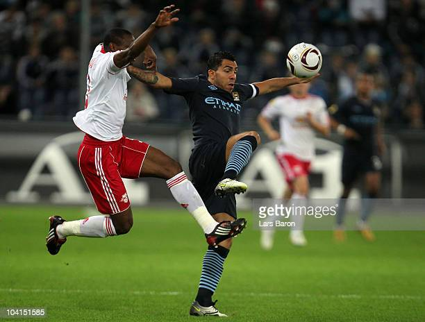 Rabiu Afolabi of Manchester challenges Carlos Tevez of Manchester during the UEFA Europa League group G match between FC Red Bull Salzburg and...