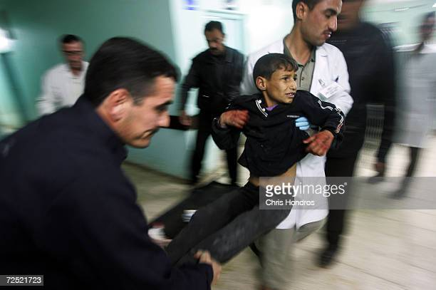 Racan Hassan is carried by hospital staff after being shot by US soldiers of the 25th Infantry Division January 18 2005 in Tal Afar Iraq The troops...