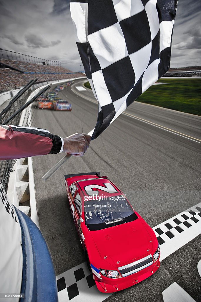 Race car crossing the finish line with flag : Stock Photo