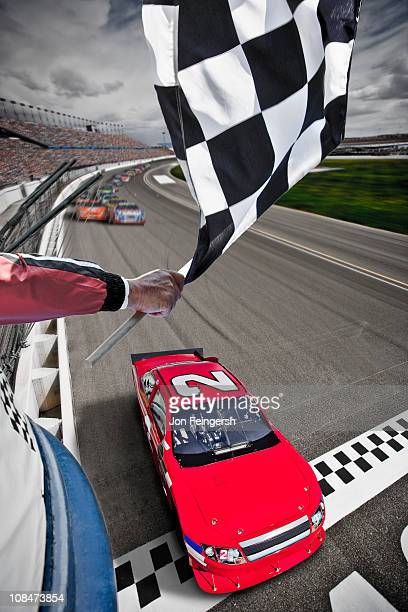 Race car crossing the finish line with flag