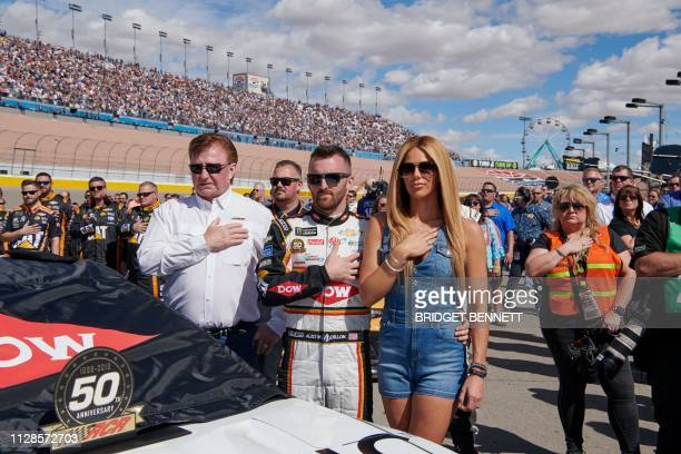 Race car driver Austin Dillon and wife Whitney Dillon place their hands over their hearts during the national anthem before the start of the Pennzoil...