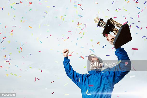 Race car driver holding trophy