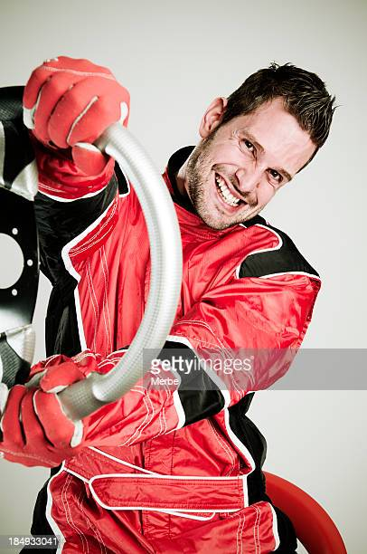 Race car driver in fire suit holding a wheel