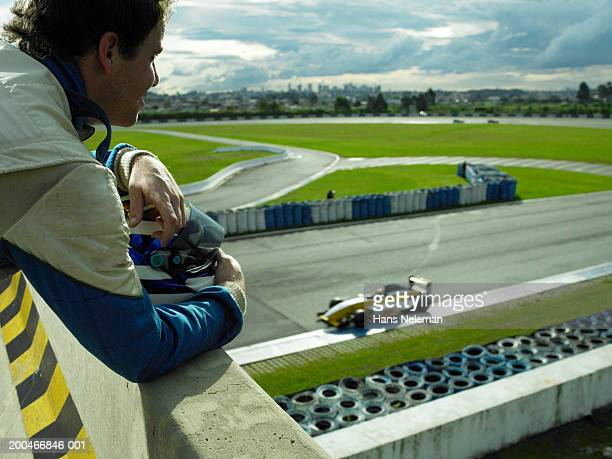 race car driver leaning over railing, side view - railings stock pictures, royalty-free photos & images