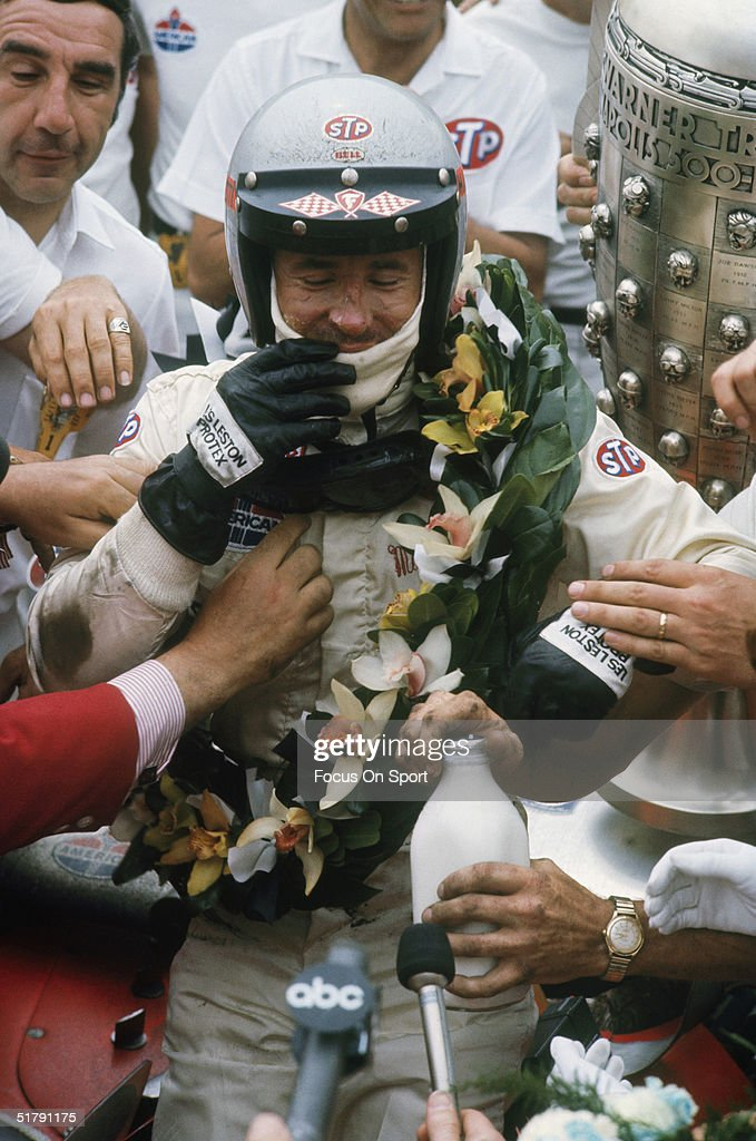 Race car driver Mario Andretti is greeted at his car with his trophy, his crew, and reporters after winning the Indianapolis 500 at the Indianapolis Motor Speedway in 1969 in Speedway, Indiana.