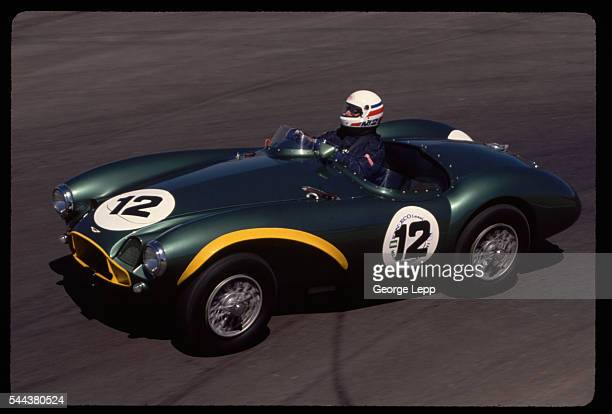 A race car driver takes a 1954 Aston martin DB3S racecar around the track at the Laguna Seca Raceway in California