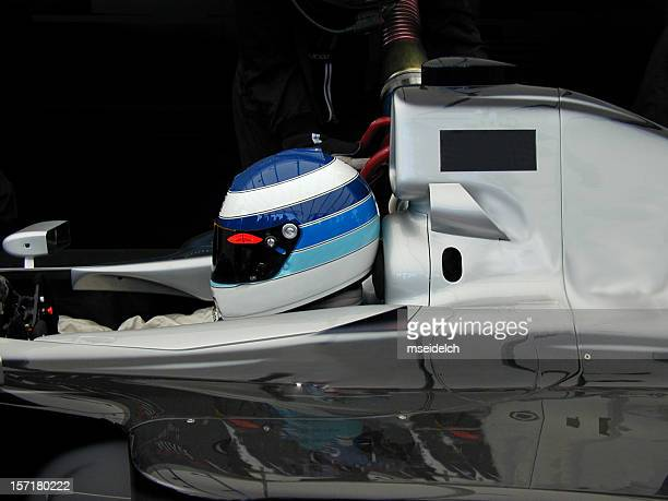 Race car driver wearing helmet and sitting in a car