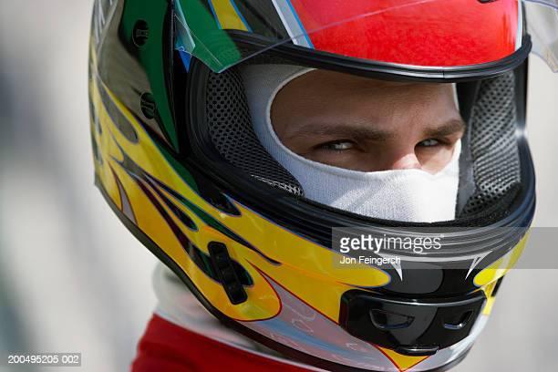 Race car driver wearing helmet, close-up, portrait