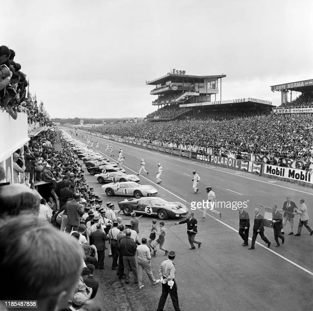Race car drivers run to their cars to take the start of the 34th edition of the 24 Hours Le Mans endurance race on June 18 on Le Mans circuit.