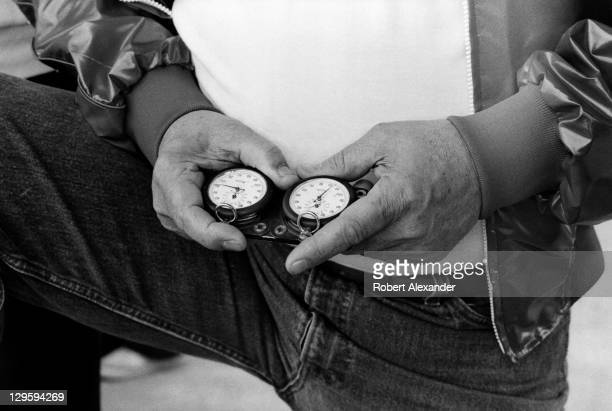 NASCAR race car owner Junior Johnson uses a stopwatch to check the speeds of cars at the Daytona International Speedway as they attempt to qualify...