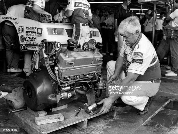 NASCAR race car owner Junior Johnson works on the engine of his No 11 Budweiser car driven by Darrell Waltrip prior to qualifying for the 1985...