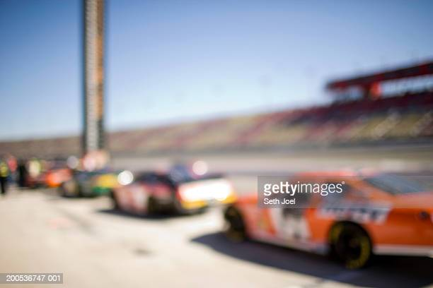 race cars lined up in pits, (defocused) - nascar stock pictures, royalty-free photos & images