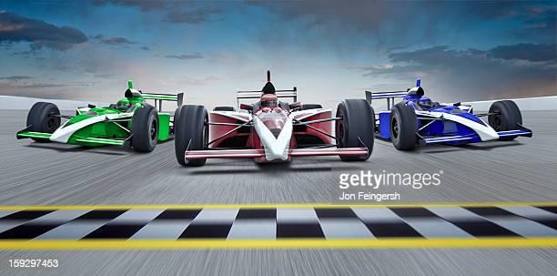 3 INDY race cars racing towards finish line.