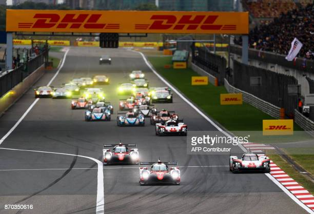 Race cars speed during the start of the FIA world Endurance Championship race in Shanghai on November 5, 2017. / AFP PHOTO / STR / China OUT