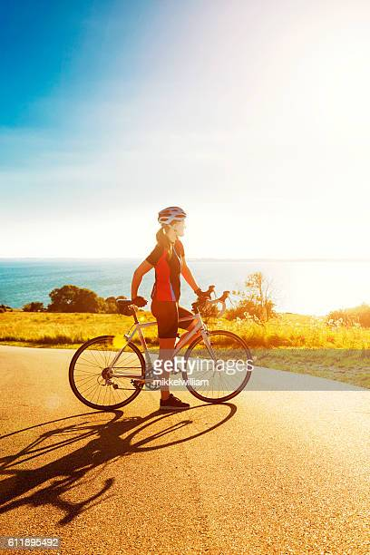 Race cyclist stands next to bike and looks at sunset